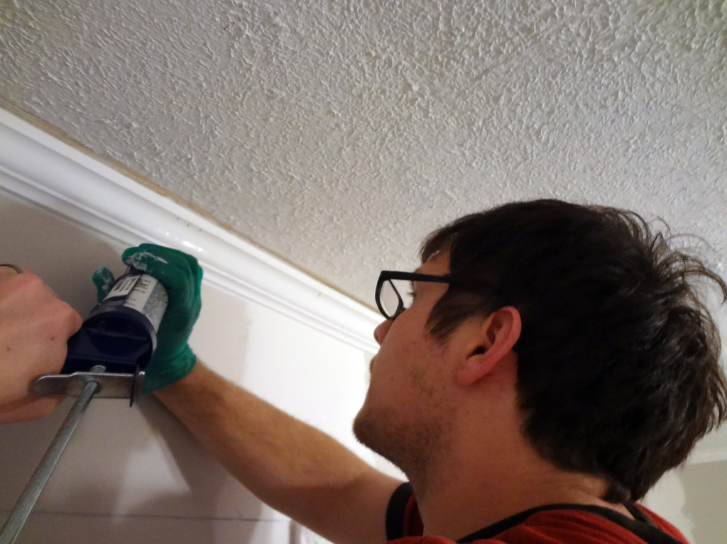 Makng over the den: caulking the trim