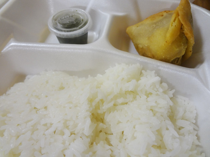 A chicken samosa with chutney and complimentary rice.